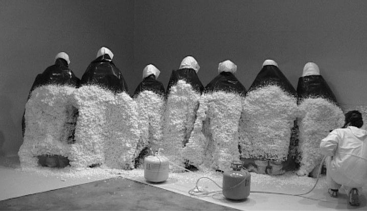 Santiago Sierra. POLYURETHANE SPRAYED ON THE BACKS OF 10 WORKERS, Lisson Gallery London, U.K., July 2004.