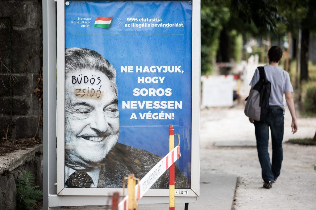 """כרזת קמפיין של ממשלת הונגריה בראשות ויקטור אורבן נגד ג'ורג' סורוס, עם הכותרת """"בואו לא ניתן לסורוס לצחוק אחרון!"""". לכרזה הוספה הכתובת """"יהודי מלוכלך"""", יולי 2017 (Akos Stiller)"""